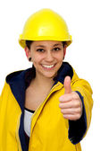 Young woman in workwear with thumb up — Stock Photo