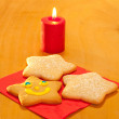 Three star shaped Christmas cookies with a candle — Stockfoto