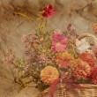 Photo: Basket of autumn flowers on textured antique background in sepia
