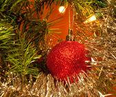 Bola navidad roja adorno en un árbol iluminado por luces de navidad — Foto de Stock