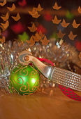 Spur and a green Christmas ball ornament — Stok fotoğraf