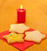 Three star shaped Christmas cookies with a candle — Stock Photo