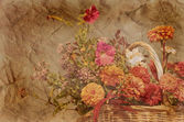 Basket of autumn flowers on textured antique background in sepia — Stock Photo