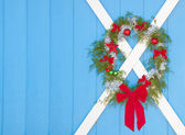 Christmas wreath hanging on a blue barn door — Stockfoto