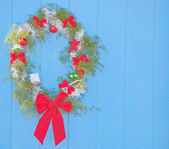 Country Christmas - wreath hanging on a blue barn wall — Stok fotoğraf