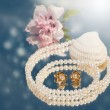 Dreamy image of golden pearl earrings with pearl necklace - Stock Photo