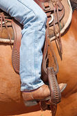 Rider's foot in stirrup in a western saddle — Stock Photo