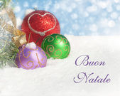 Colorful Christmas ornaments in snow with text Buon natale — Stock Photo