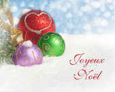 Dreamy image of colorful Christmas ornaments in snow — Stock Photo