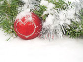 Christmas wreath and red bauble with a heart in snow — Stock Photo