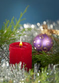 Red Christmas candle burning, surrounded by evergreen — Stock Photo