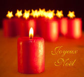 Red Christmas candle - with group of similar candles on background — Stock Photo