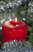 Kırmızı christmas mum parlak gümüş tinsel tarafından çevrili yanma — Stok fotoğraf