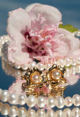 Pearl ear rings with pearl necklace and a hibiscus blossom — Stock Photo