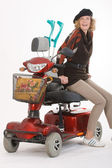 Disabled elderly woman with scooter — Stock Photo