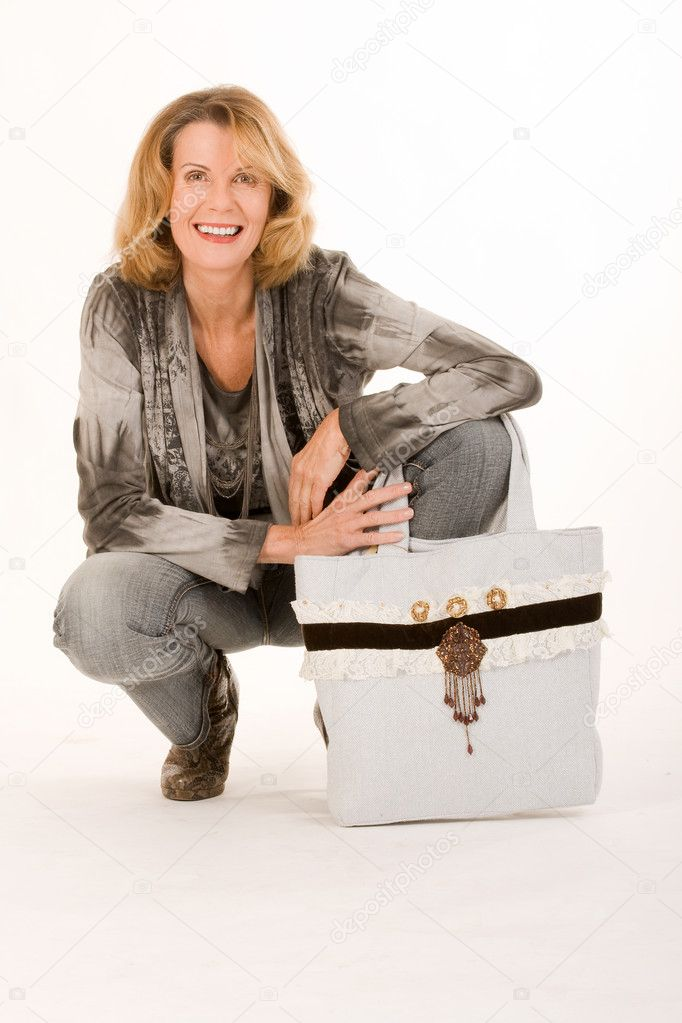Older woman with a fashionable bag is kneeling on the ground — Stock Photo #8152571