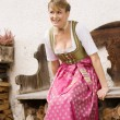 Bavarian girl in traditional dress at a bank — Stock Photo