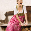 Stock Photo: Bavarian girl in traditional dress at a bank