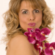 Woman portrait with orchid and kiss — Stock Photo