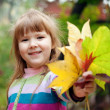 Smiling girl with fallen leaves — Stock Photo