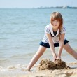 Little girl playing at the seaside — Stock Photo #10413353