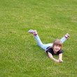 Young smiling girl lying on a lawn — Stock Photo #10413373