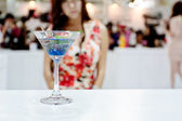A glass of blue coctail (Ole) with sexy girl on background — Stock Photo