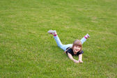 Young smiling girl lying on a lawn — Stock Photo