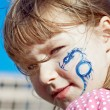 Portrait of a little girl with blue dragon on her face — Stock Photo