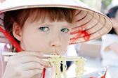 Young girl eating spaghetti in restaurant — Stock Photo