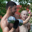Stock Photo: Father and son train with dumbbells
