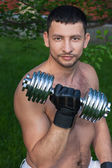 Man lifting free weights outside — Stock Photo