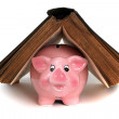 Pink piggy bank under old book — Stock Photo