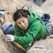 Female climber clinging to a cliff. - Stock Photo