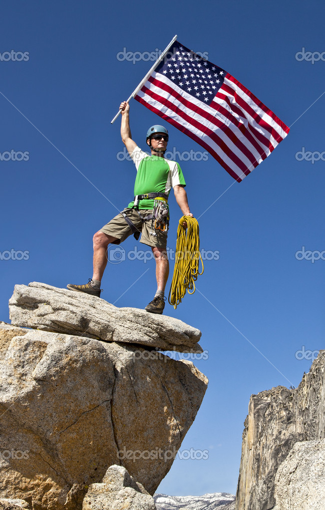 Climber waves an american flag on the summit after a challenging ascent. — Stock Photo #10643476