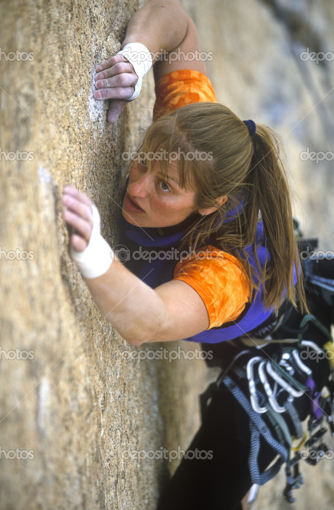 Female rock climber struggles to reach her next grip as she battles her way up a challenging cliff. — Stock Photo #9180302