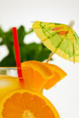 Refreshing orange drink with a straw and umbrella — Stock Photo