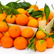 Box full of fresh mandarin with green leaves — Stock Photo #8666499