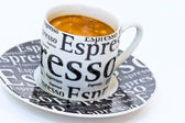 Cup fresh espresso coffee with crema on the black saucer — Stock Photo