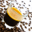 Hot espresso coffee surrouded by group of coffee beans - Stock Photo