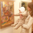 Young mother shows to the baby a picture at an exhibition - Stock Photo