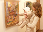 Young mother shows to the baby a picture at an exhibition — Stock Photo