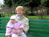 The grandmother with the granddaughter sit on a bench in park — Stok fotoğraf
