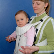 The woman keeps the baby in a baby sling — Stock Photo