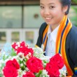 Graduated girl with red rose — Stock Photo