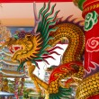 Golden dragon statue on pillar - Stock Photo