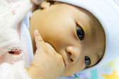 Asian female baby sucking her fingers — Stock Photo