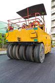 Steamroller on asphalt road from back — Stock Photo
