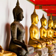 Black Buddha statue among other golden — Stockfoto