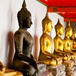 Black Buddha statue among other golden — Стоковая фотография